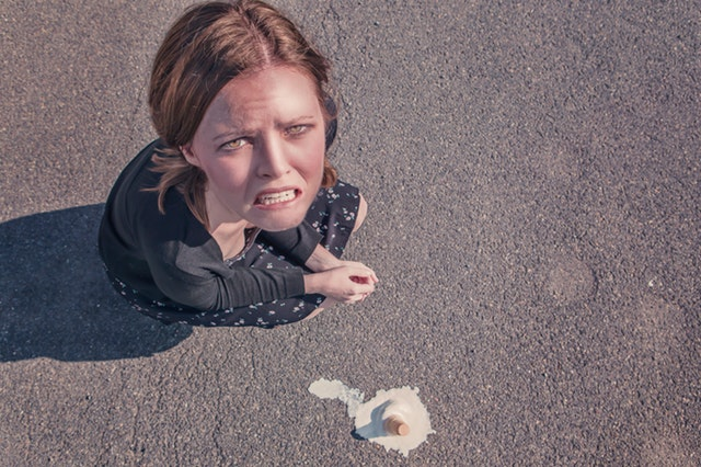 woman crouched down next to a fallen ice cream cone